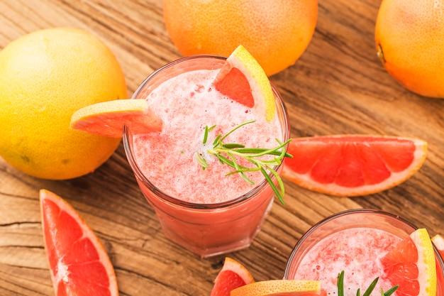 Grapefruitsaft mit rosmarin und eis in einem glas auf dem tisch.