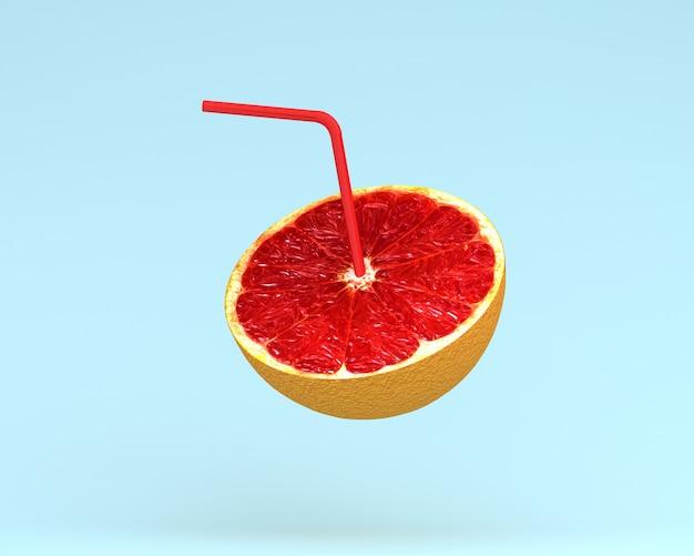 Grapefruitsaft, orange scheibe mit stroh auf blauem pastellhintergrund. minimales fruchtkonzept