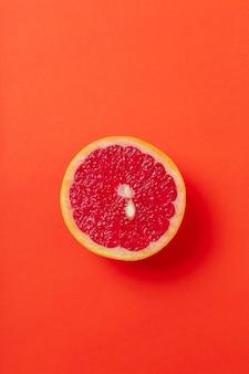 Grapefruitscheibe isoliert auf roter oberfläche