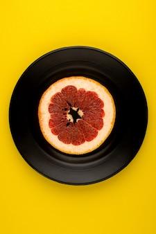 Grapefruitscheibe orange reif weich saftig in schwarzer platte auf dem gelben boden