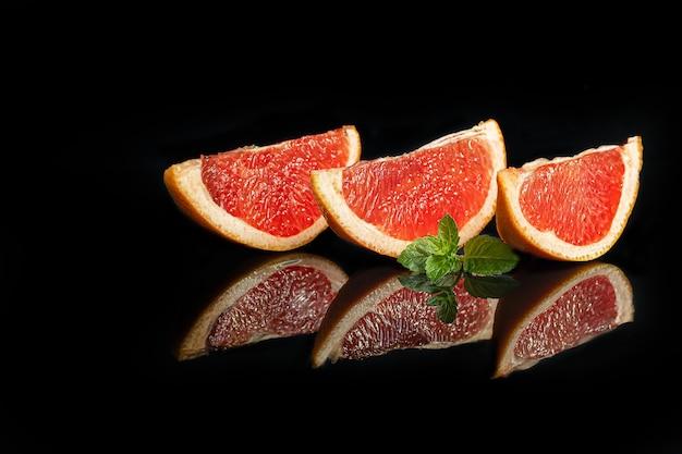 Grapefruitscheiben auf dunklem hintergrund mit einem zweig minze. isolieren. platz kopieren.