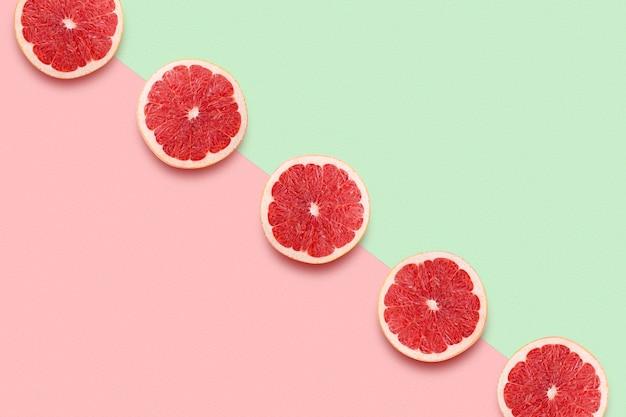 Grapefruitscheiben in reihe auf pastellrosa und grünem tisch