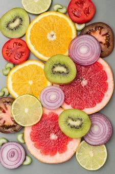 Grapefruitscheiben und rote zwiebeln. farbiges abstraktes stillleben. flach liegen. grauer hintergrund.