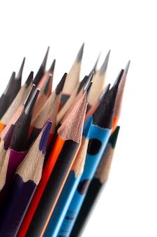 Graphitstifte zum schreiben und zeichnen zusammen mit mehrfarbigen stiften auf weißem schreibtisch