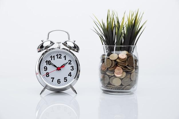 Gras wächst aus münzen in bank und wecker.