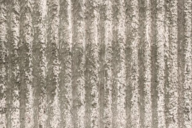 Grau-beige wand mit einem dekorativen putz und vertikalen streifen. textur für den hintergrund.