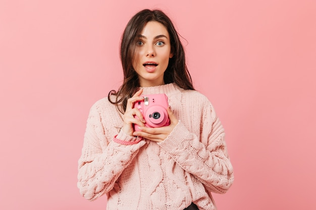 Grauäugige dame mit erstauntem ausdruck macht ein foto auf einer rosa minikamera. frau mit dem geraden dunklen haar im gestrickten pullover, der auf einem isolierten hintergrund aufwirft.