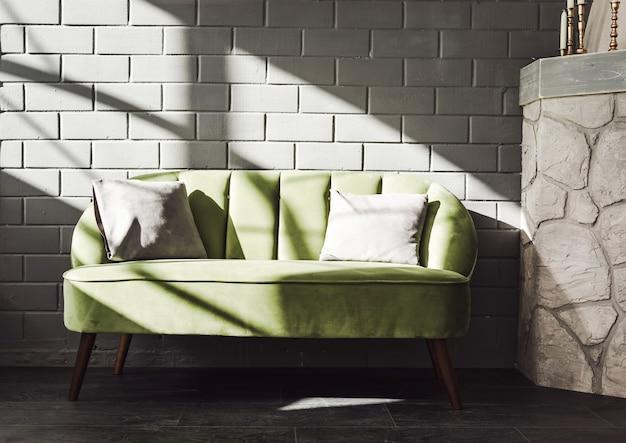 Graue backsteinmauer, grünes sofa, sonnenlicht