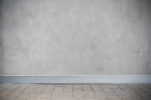 Graue betonmauer mit schmutzboden