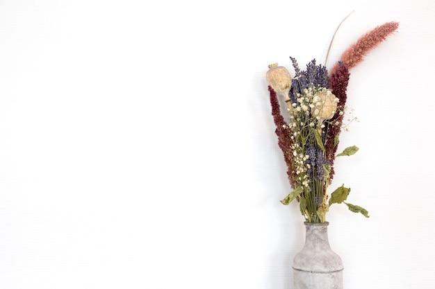 Graue betonvase mit hellen getrockneten blumenstraußblumen vor der modernen wanddekoration der weißen wand von