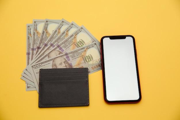 Graue brieftasche, dollarnoten und handy lokalisiert auf gelb