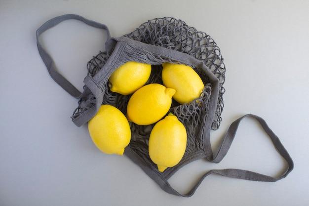 Graue einkaufstasche aus mesh mit zitrone auf dem grauen hintergrund. kein plastiktüten-konzept. nahaufnahme. ansicht von oben.