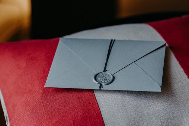 Graue einladungskarte für hochzeit oder besonderen anlass auf rotem und weißem kissen. hochzeitsdekor.