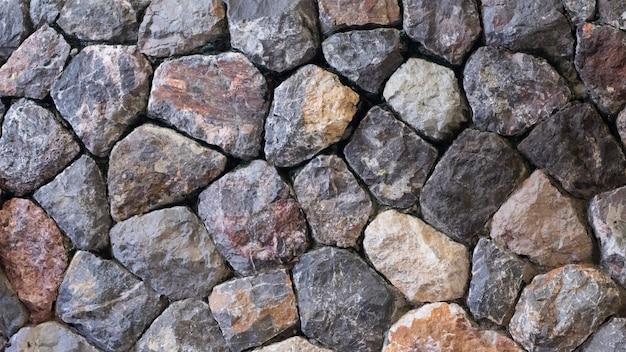 Graue farbe der dekorativen dreal steinwandoberfläche des rustikalen landhausstildesigns mit zement. hintergrund der alten steinmauer. textur der alten.