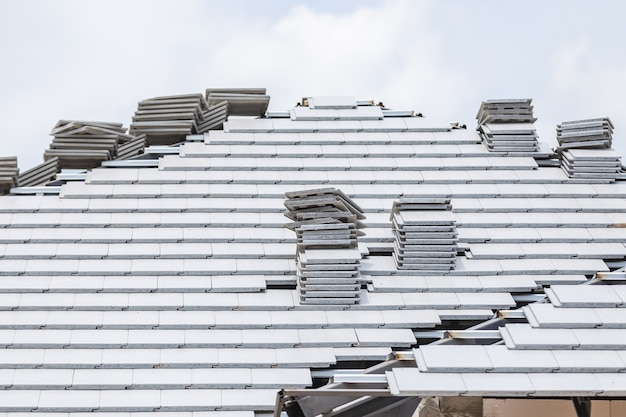 Graue farbe des ziegeldaches im bau mit stapeln auf dach