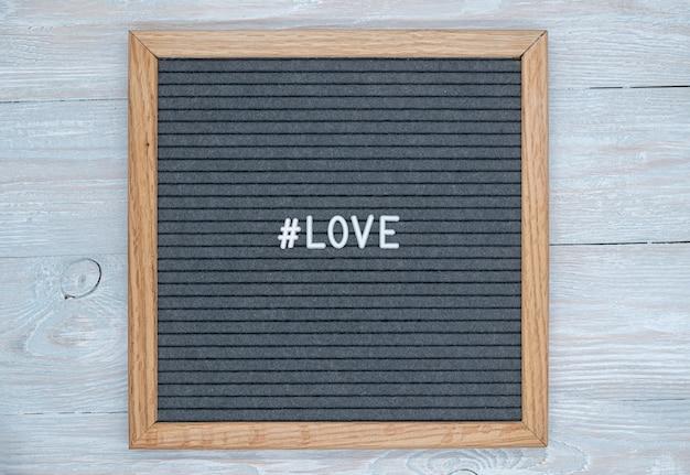 Graue filzbrettbuchstaben mit dem englischen wort liebe und dem zeichen des hashtags