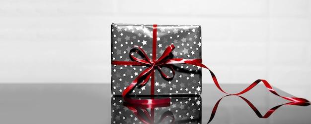 Graue geschenkbox mit roter schleife auf schwarzem glas, hintergrund von weiß. feiertage oder black friday-konzept.