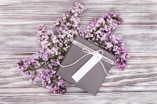 Graue geschenkbox und lila blumen.