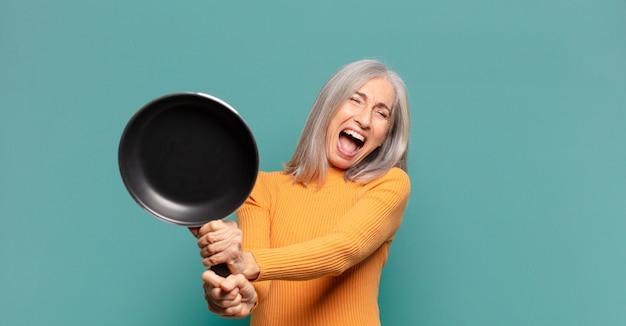 Graue haare hübsche frau mittleren alters, die koch mit einer pfanne lernt