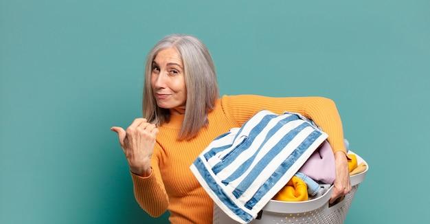 Graue haare hübsche haushälterin beim wäschewaschen