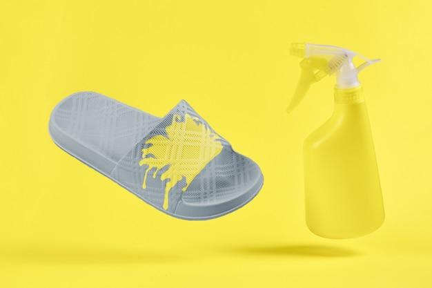 Graue hausschuhe mit reinigungsspray auf gelbem hintergrund. konzept trendige farben 2021 jahre. nahansicht.