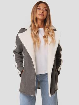 Graue jacke, weißes t-shirt darunter, moderne jeans an diesem hübschen mädchen. hipster junge frau im kausalen blick.