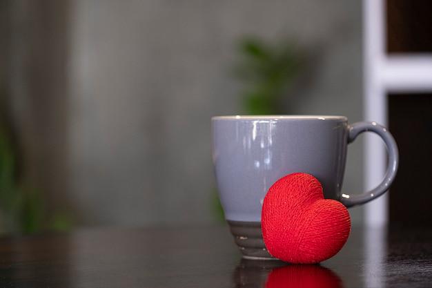 Graue keramische kaffeetasse und rotes herz