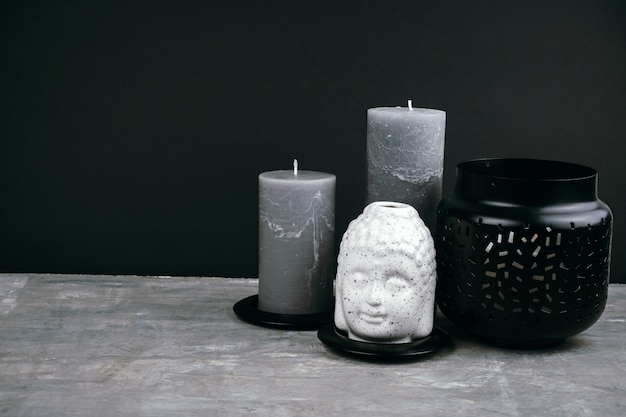 Graue kerzen und weißer keramik-buddha-kopf auf einem tisch gegenüber schwarzer wand