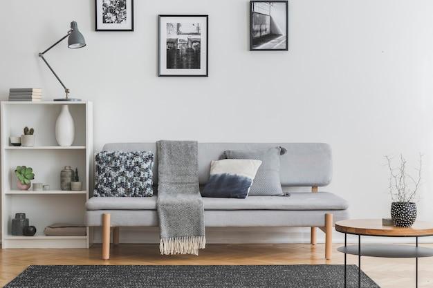 Graue lampe auf weißem bücherregal mit vasen und büchern neben elegantem sofa