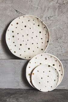 Graue leere platten (keramik) auf einem grauen steinhintergrund. graues minimalismuskonzept