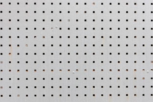 Graue metallplatte mit quadratischen schwarzen löchern