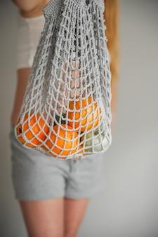 Graue netztasche mit nahaufnahme aus gelben orangen und kopierraum. handgemachte öko-tasche in der hand