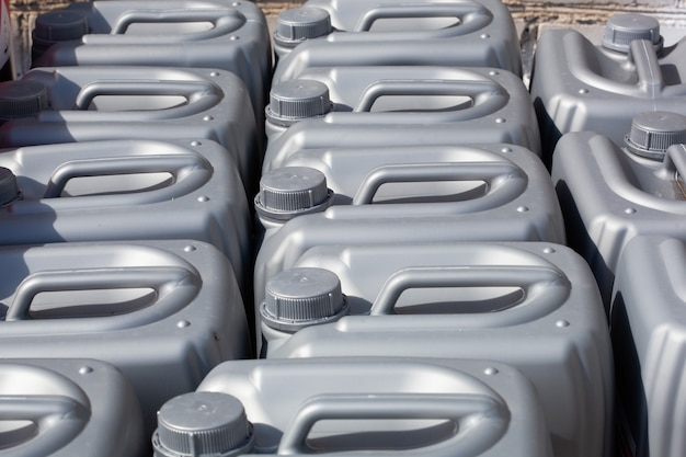 Graue plastikkanister im lager, in der produktion, in der fabrik. oberfläche aus kunststoffkanistern