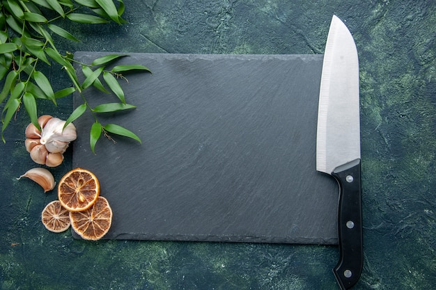 Graue platte der draufsicht mit großem messer auf dunkelblauem hintergrundfarbfoto kochen blauen meeresfrüchte-küchenschreibtisch