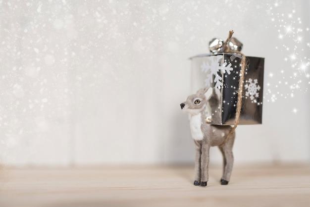 Graue rotwild, die ein weihnachtsgeschenk mit kopienraum tragen