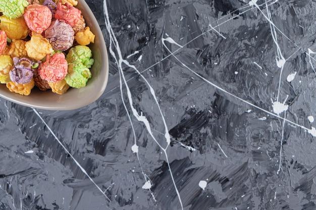 Graue schale der köstlichen bunten popcorns auf marmortisch.
