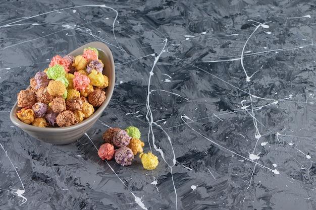 Graue schüssel der köstlichen bunten popcorns auf marmorhintergrund.