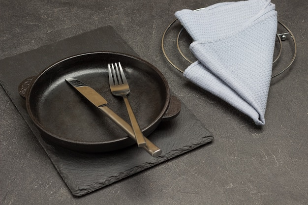 Graue serviette auf dem tisch. löffel und gabel in eine leere gusseiserne pfanne geben. schwarzer hintergrund. ansicht von oben
