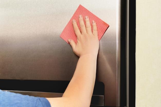 Graue silberne kühlschrank der hand der frau, die mit rosa lappen reinigt