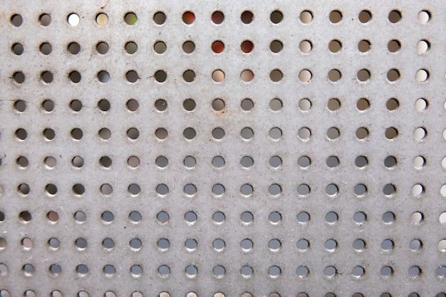 Graue stahloberfläche mit kleinen runden löchern