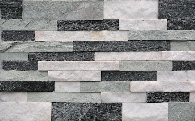Graue steinfliesenbeschaffenheitsbacksteinmauer