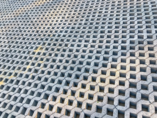 Graue steinziegelsteinfliese mit grünem gras und sand als hintergrund oder textur.