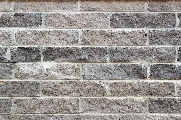 Graue steinziegelwandbeschaffenheit. abstrakter steinziegelhintergrund