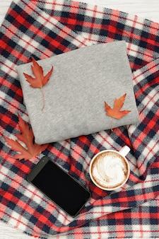 Graue strickjacke, plaid, kaffeetasse und intelligentes telefon. herbstblätter