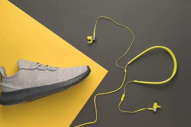 Graue turnschuhe und gelbe kopfhörer auf gelbem und grauem hintergrund. sportlicher lebensstil. farben 2021.