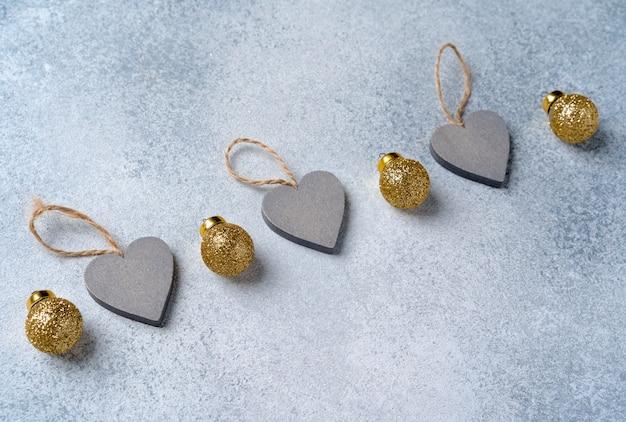 Graue und goldene weihnachtskugeln auf gefrostetem tisch