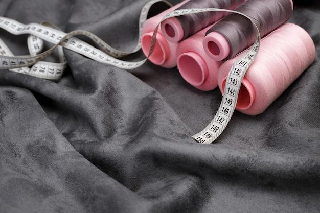 Graue und rosa fäden mit einem zentimeter auf einer grauen oberfläche