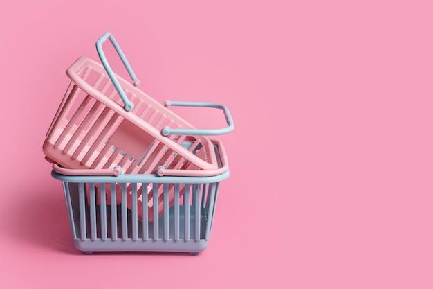Graue und rosa plastikeinkaufskörbe einzeln auf rosa hintergrund mit kopienraum