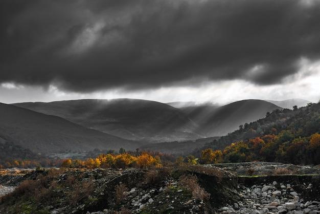 Graue wolken über herbstlichem bergwald