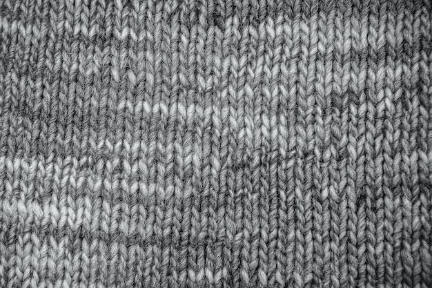 Graue wollschalbeschaffenheit schließen oben. gestrickter jersey-hintergrund mit reliefmuster. zöpfe im maschinenstrickmuster